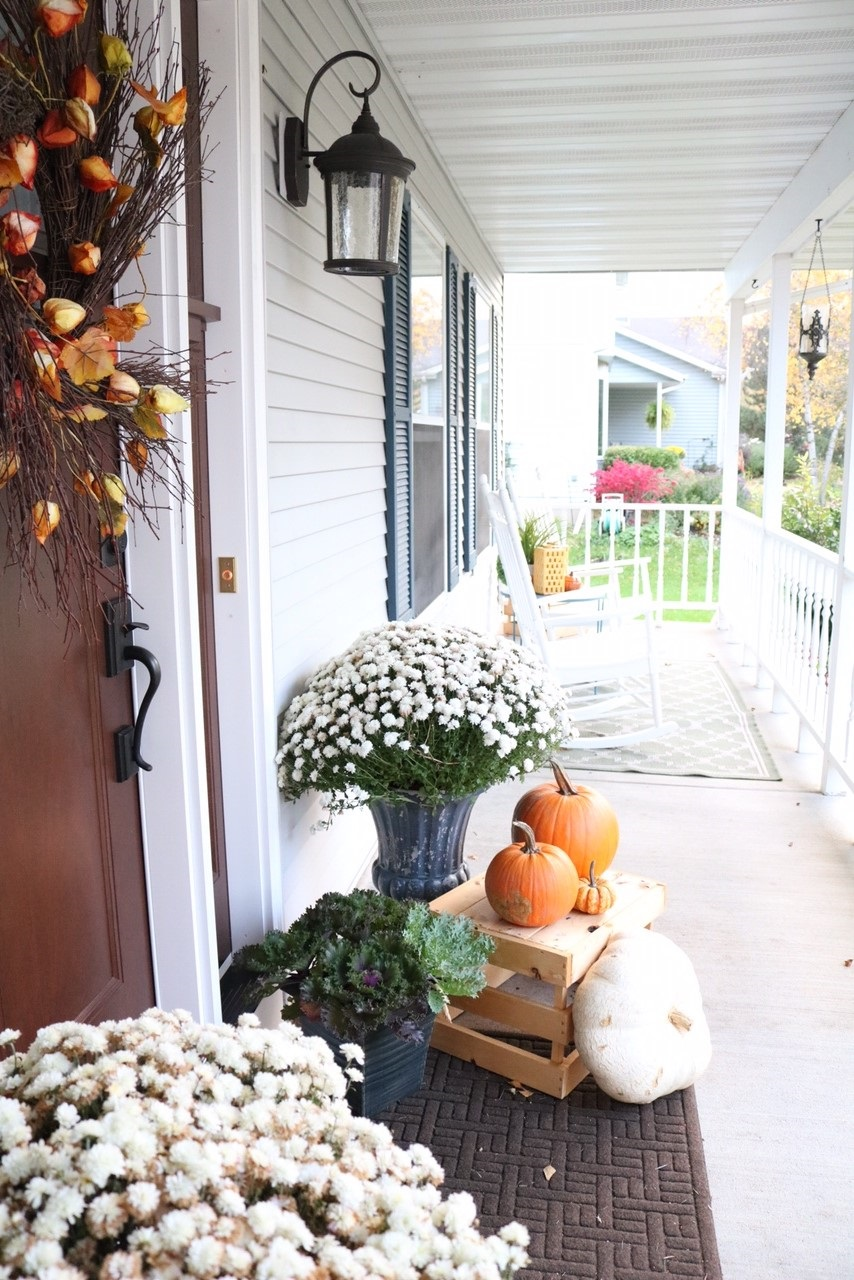 Fall Front Porch Inspiration | Pumpkins, door wreath with branches, kale planters, apple crates, mums, and cornstalks!